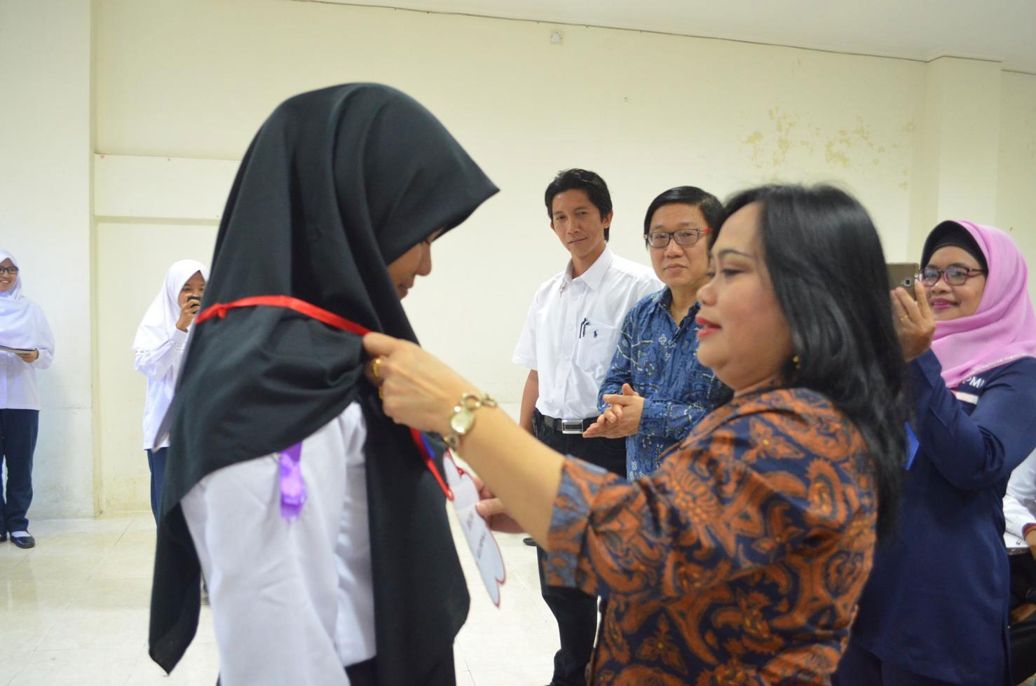 Dekan FKM Hanifa Maher Denny mengalungkan tanda peserta kepada perwakilan KSR PMI sebagai tanda dimulainya kegiatan Pendidikan dan Pelatihan 120 Jam Bagi Calon Anggota Korps Sukarela (KSR) PMI Unit FKM UNDIP, Rabu (1/02) di Kampus FKM Undip Tembalang.